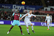 Gylfi Sigurdsson of Swansea city ® is challenged by Cheikhou Kouyate of West Ham Utd. Barclays Premier league match, Swansea city v West Ham Utd at the Liberty Stadium in Swansea, South Wales  on Sunday 20th December 2015.<br /> pic by  Andrew Orchard, Andrew Orchard sports photography.