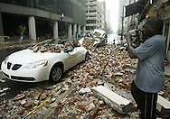 A man videotapes a car crushed by the front of a building in downtown New Orleans, after Hurricane Katrina hit, August 29, 2005. REUTERS/Rick Wilking
