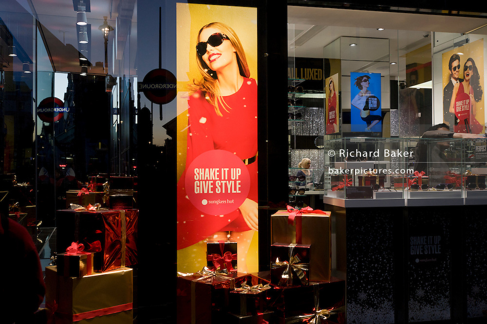 Window display and a poster girl for Burberry sunglasses they call Eyewear, in a sunlit London street.