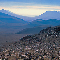 An archaeology team led by Dr. Johan Reinhard hikes up the slopes of 22,110-foot Volcan Llullaillaco in northern Argentina, where they they later found the world's highest mummies from an ancient Inca sacrifice. In the background are other lonely mountains and volcanoes of the vast South American Altiplano.