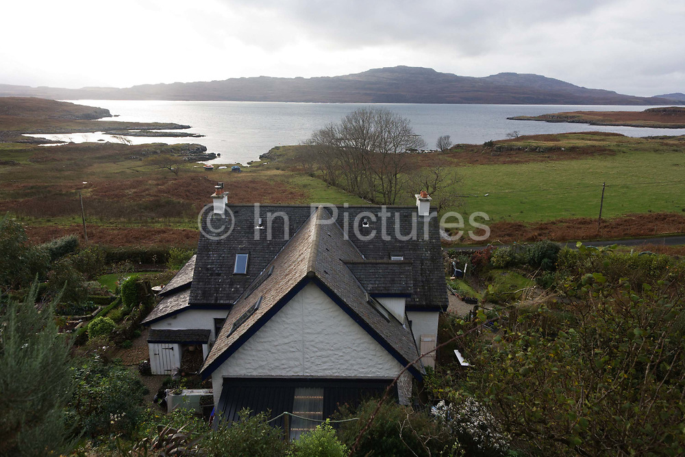 """An aerial landscape looking down to the remote Lip na Cloiche, a garden, arts shop and bed+breakfast cottage run by Lucy McKenzie, near Ulva ferry, Isle of Mull, Scotland. Beyond is Loch Tuath and the headland of the Island of Ulva. Lip na Cloiche is a small, densely-planted garden on the Isle of Mull, open to the public. Lip na Cloiche garden is beautifully situated close to the shoreline of the Isle of Mull, and has stunning views of Loch Tuath and the Isle of Ulva. A wide range of such plants is available for sale throughout the year, as well as fresh eggs and many craft items made from locally """"found"""" materials. There is no admission charge. http://www.lipnacloiche.co.uk"""