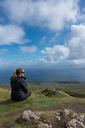 A lady sits over looking the Trotternish peninsula at The Old Man of Storr on the 3rd September 2016 on the Isle Of Skye in Scotland in the United Kingdom. The 'Old Man' is a large pinnacle of rock that stands high and can be seen for miles around. Forming part of the Trotternish ridge, the Storr was created by a massive ancient landslide, and has become a popular walking and tourist destination.
