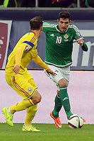 ROMANIA, Bucharest : Romania's Vlad Chiriches (L) and Northern Ireland's Kyle Lafferty (R) vie for the ball during the Euro 2016 Group F qualifying football match Romania vs Northern Ireland in Bucharest, Romania on November 14, 2014.