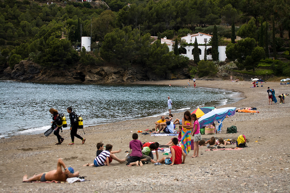 Scuba divers walk on the beach in front of El Bulli restaurant near Rosas on the Costa Brava, Northern Spain