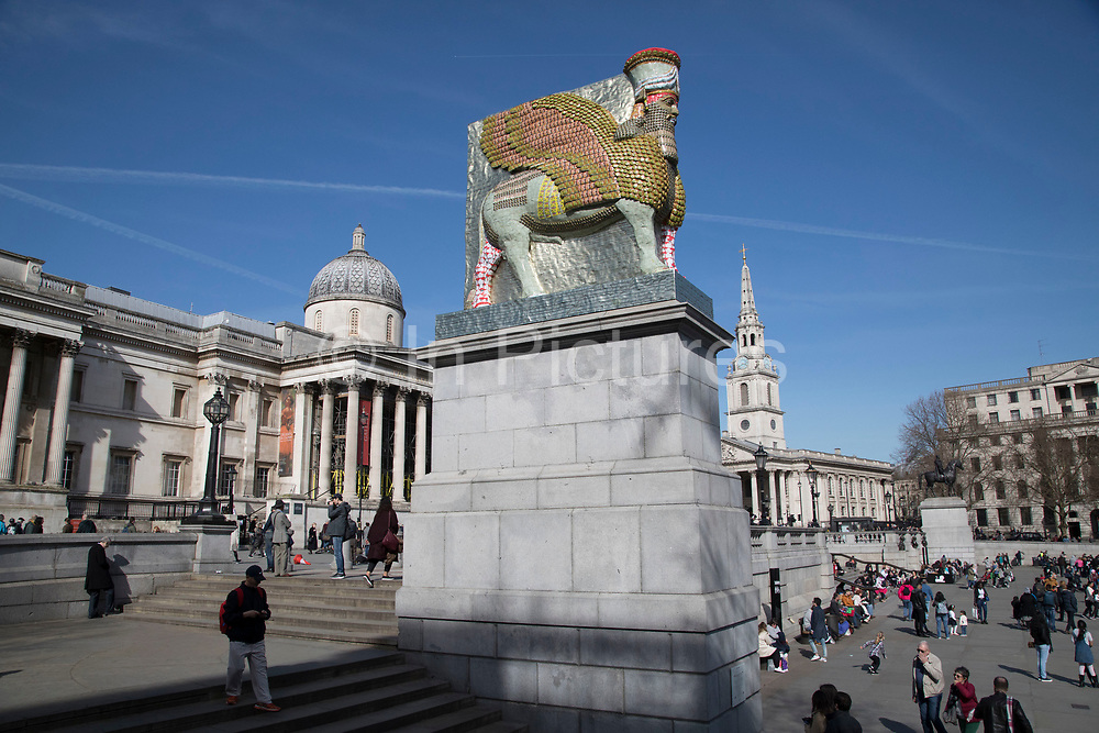 The 12th Fourth Plinth sculpture named 'The Invisible Enemy Should Not Exist' by artist Michael Rakowitz, in Trafalgar Square, on 5th April 2018 in London, United Kingdom. The artwork attempts to recreate more than 7,000 objects which have been lost forever. Some were looted from the Iraq Museum in 2003, while others were destroyed at archaeological sites across the country during the Iraq War. Rakowitz has recreated the Lamassu. This winged bull and protective deity guarded the entrance to Nergal Gate of Nineveh from 700 BC until it was destroyed by Daesh in 2015. The Fourth Plinth is an empty plinth in Trafalgar Square in central London originally intended to hold an equestrian statue. For over 150 years there was much squabbling about what to do with the fourth plinth, but very little agreement, until the temporary use of the plinth to display three pieces of art in the last years of the 20th century lead to a commission being formed to decide on a use for it. Eventually that commission unanimously decided to use it for the temporary display of artworks.