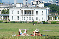 © Licensed to London News Pictures 18/07/2021. Greenwich, UK. A couple relaxing in Greenwich Park, London as the hot  heatwave weather continues today with temperatures expected to hit 30C. Photo credit:Grant Falvey/LNP