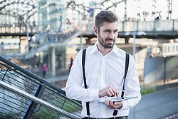 Businessman standing against railing and working on digital tablet, Munich, Bavaria, Germany