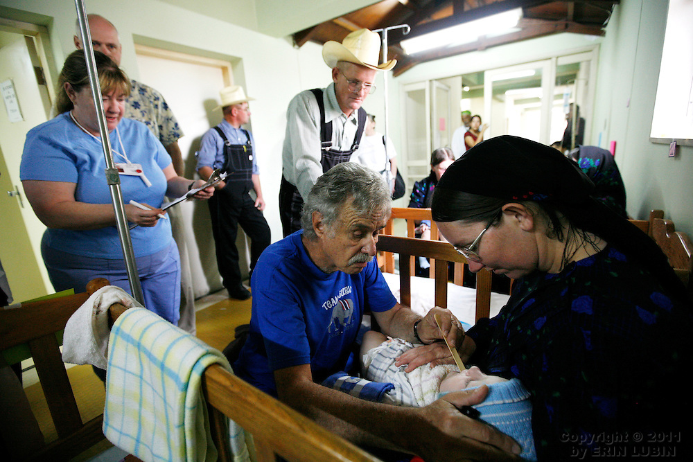 Operation Smile volunteer plastic surgeon, Harold Rosenfield from California, checks on patient #89 Maria Neustaeter, 11 months old, 12 hours by bus, the morning after her surgery with Operation Smile, November 14, 2007, at the Hospital Japones in Santa Cruz, Bolivia..During Operation Smile's World Journey of Smiles...Photograph by Erin Lubin.