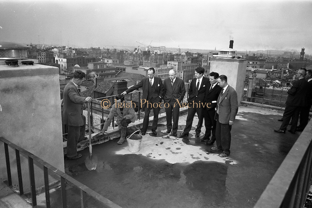 """18/04/1963<br /> 04/18/1963<br /> 18 April 1963<br /> """"Topping Off"""" Jury's Hotel new extension. Watching John McCale (Cabe?) and Tony O'Neill """"Topping Off"""" the 100ft high new extension to Jury's Hotel were (l-r) Joseph Kidney , Kidney and Co. architects; John O'Brien, Chairman; Paul Burke Kennedy, Kidney and Co.; Wilhelm Opperman, General Manager, Jury's Hotel Ltd. and Dick Hendrick, General Foreman on the site."""