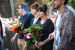 © Licensed to London News Pictures. 03/06/2018. London, UK. People with flowers watch on as people mark the anniversary of the London Bridge and Borough Market terror attacks. A series of events have taken place throughout the day, including a service of commemoration at Southwark Cathedral, the planting of an olive tree in the Cathedral grounds, a minute's silence at 4:30pm and the laying of flowers.  Photo credit : Tom Nicholson/LNP