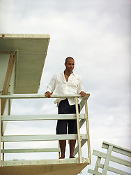 man looking down from a lifeguard stand in California