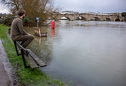 © Licensed to London News Pictures. 04/02/2021. London, UK. A man sits on top of a bench as the River Thames at Chertsey continues to rise. Flooding in parts of  Laleham and Chertsey in Surrey as rising flood water continues to rise around riverside properties in the area. The Uk is set to be battered by heavy rainfall, flooding and snow storms this weekend as the Met Office issue warnings that snow could hit most of the country in the coming days. Photo credit: Alex Lentati/LNP