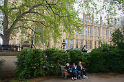 Women eating a picnic on a bench under the Palace of Westminster in central London. The three women sit side by side on the seat at the entrance of Victoria Tower Park, beneath the Gothic architecture of Victoria architect Pugin's building, the seat of parliamentary government in the UK.