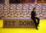 A man sits down on a 'Sit down' sign located at the entrance of an arena in Manchester. The arena is hosting the 2006 Creative Partnerships Exciting Minds conference. The creative Partnerships aims to enhance the achievement, motivation, creative skills and employability of young people