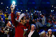 Fans use their mobile phone lights as the hall lights go down during the PDC World Championship darts at Alexandra Palace, London, United Kingdom on 14 December 2018.