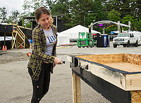Kayla Mecum paints the beer tubs on Thursday afternoon at the Weirs Beach Drive In Theater in preparation for Laconia Fest.  (Karen Bobotas/for the Laconia Daily Sun)