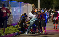 August 18, 2018 - Wellington, Florida, U.S. - A gunshot victim is helped outside the fence near the south end zone at Palm Beach Central High School. Two adults were shot Friday night at a football game between Palm Beach Central and William T. Dwyer high schools, authorities said. The gunfire sent players and fans screaming and stampeding in panic during the fourth quarter of the game at Palm Beach Central High School in Wellington, Florida on August 17, 2018. (Credit Image: © Allen Eyestone/The Palm Beach Post via ZUMA Wire)