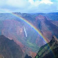 Waipo`o Falls in Waimea Canyon, Kokee State Park, on the Hawaiian island of Kauai shows a rainbow in a light rainshower