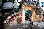 A young vietnamese boy walks through an ancient doorway, Hue, Vietnam, Southeast Asia