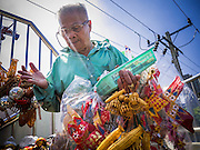 12 JANUARY 2013 - BANGKOK, THAILAND:  A souvenir vendor crosses Sukhumvit Soi 77 on a pedestrian overpass bridge carrying a load of souvenirs and toys.     PHOTO BY JACK KURTZ