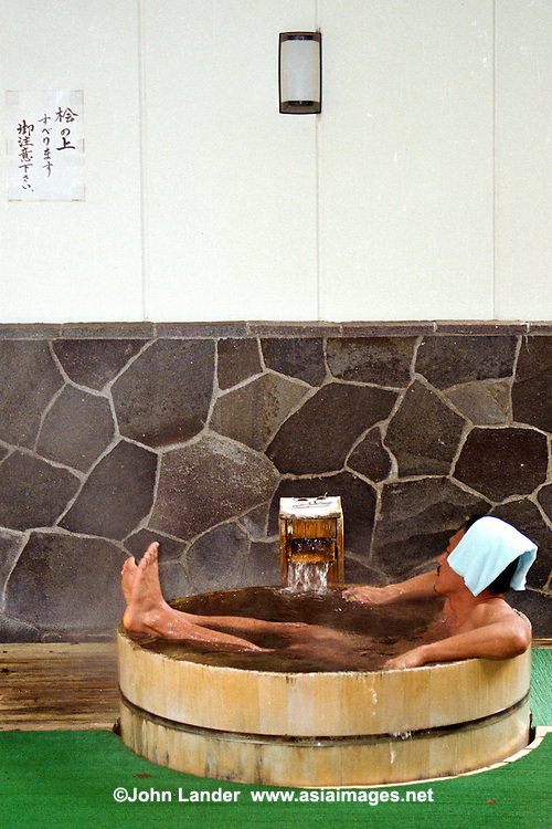 A man in a cedar tub at Hakone Hot Springs.  Hakone is one the largest concentrations of geothermal activity in Japan located near Mount Fuji. MODEL RELEASED