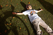 Wearing a safety helmet and t-shirt , a nine year-old girl cyclist pretends to be asleep, having has collapsed on the grass at Peckham Rye Park in South London after a marathon ride into the centre of London. 'Freewheel' was a Hovis-sponsored event for riders and families to enjoy a day of traffic-free cycling through the capital's streets and this girl has ridden 18 miles on this late-summer Sunday - starting and finishing in this park. The shadow of a rear bicycle wheel can be seen to her right and she feigns death by spreading out on the grass, pretending to sleep before reviving herself with a drink and pedalling on home, yet another mile away.