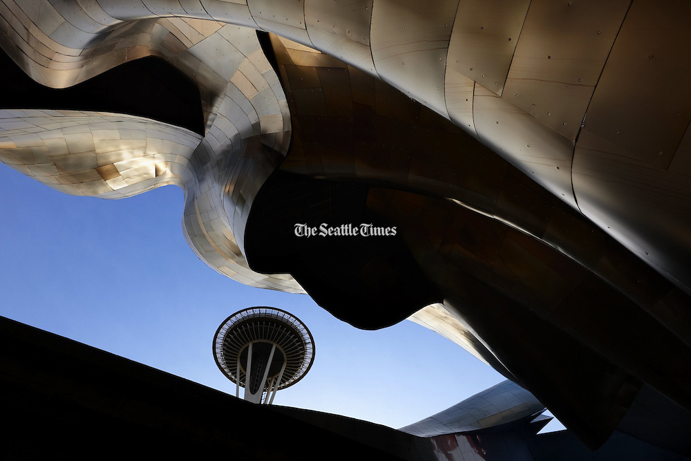 Seattle's most widely known architectural icon, the Space Needle, peeks between the tracks of the monorail and the undulating metal sides of the EMP, which has become an icon in its own right. (Benjamin Benschneider / The Seattle Times)
