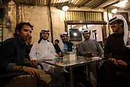 A group of young men  from Saudi Arabia and Kuwait enjoy cups of hot tea and water at an outdoors cafe in Souq Waqif in Doha, Qatar.