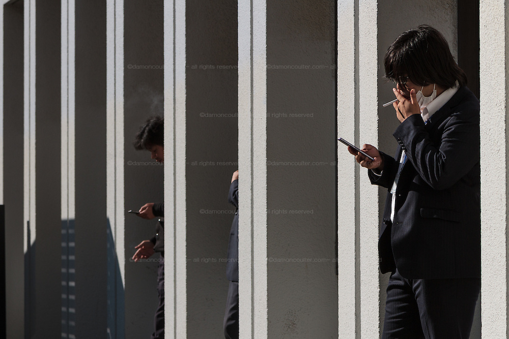 Japanese male office workers or salarymen smoke outside a building in Jimbocho, Tokyo, Japan. Friday December 18th 2015