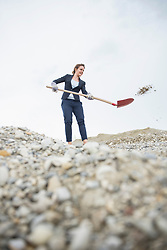 Businesswoman throwing stones with a shovel, Munich, Bavaria, Germany, Europe