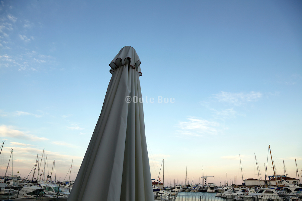 parasol and sailing boats masts during sunset