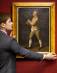 © Licensed to London News Pictures. 24/01/2013. London, UK. A Bonham's employee hangs an extremely rare English School portrait of boxer George 'the Coachman' Stevenson (1742) (est. GB£10,000-15,000), the death of whom prompted boxer Jack Broughton to draw up the first universal boxing rules, at the press view for the 'Bonham's Gentleman's Library Sale' in Knightsbridge, London, today (24/01/13). The sale, made up of weird, wonderful, rare and practical items, - all fit for a gentleman's library - is set to take place at 10am on the 24th of January at the auction house's Knightsbridge premises. Photo credit: Matt Cetti-Roberts/LNP