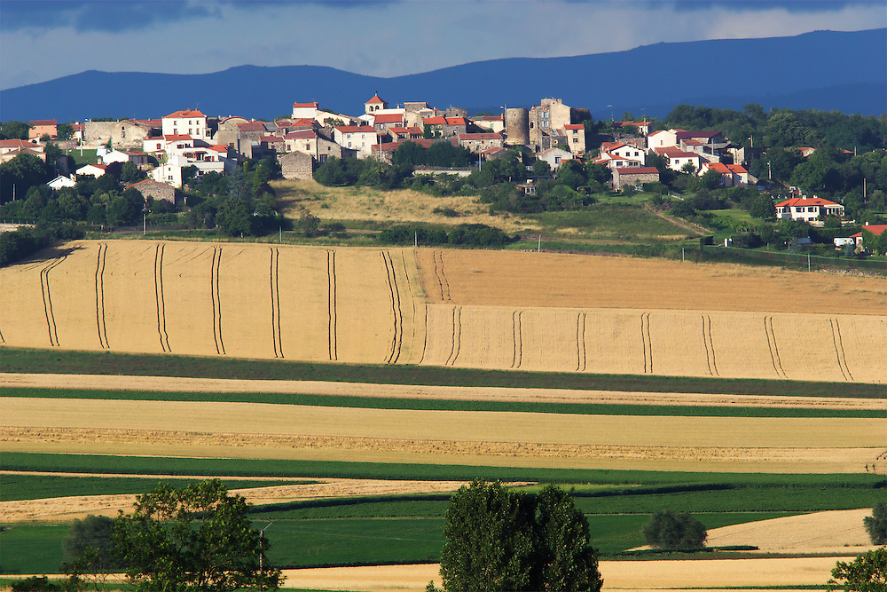 Village sight with farmers fields infront.  Solignate, Auvergne, France