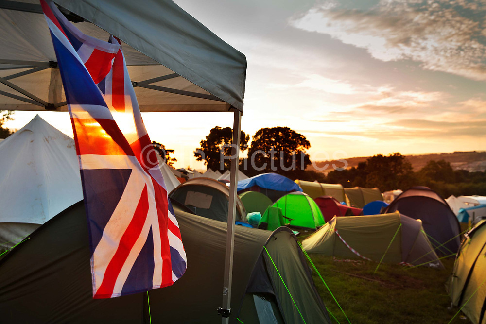 Union Jack flag hanging from a tent in the Shangri La camping field, Glastonbury Festival 2016.<br />  The Glastonbury Festival is the largest greenfield festival in the world, and is now attended by around 175,000 people. Its a five-day music festival that takes place near Pilton, Somerset, United Kingdom. In addition to contemporary music, the festival hosts dance, comedy, theatre, circus, cabaret, and other arts. Held at Worthy Farm in Pilton, leading pop and rock artists have headlined, alongside thousands of others appearing on smaller stages and performance areas.