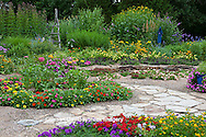 63821-21912 Flower garden with stone paths, blue pots, birdhouse, obelisk.  Black-eyed Susans (Rudbeckia hirta), zinnias, red & purple verbenas (Verbena canadensis), New Gold Lantana (Lantana camara), Petunias, butterfly bushes, Marion Co., IL