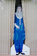 As if parting the blinds of a high-street business, a life-size cut-out of a Pakistan Airlines (PIA) air hostess is propped up in the window of Lumb Lane travel agency, Bradford, Yorkshire.