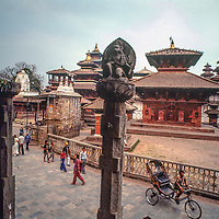 Early morning visitors pass through Durbar Square in Kathmandu, Nepal, 1982.  Today the streets are packed with cars and scooters.