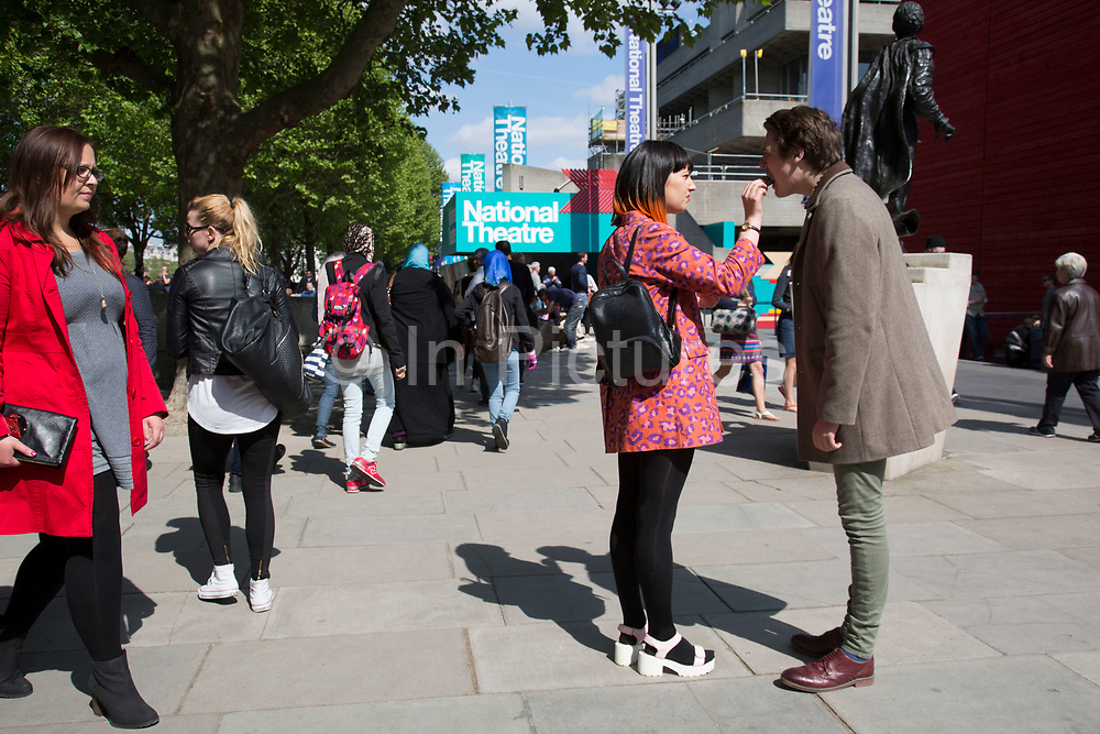 A woman feeds her boyfriend a piece of cake. The South Bank is a significant arts and entertainment district, and home to an endless list of activities for Londoners, visitors and tourists alike.