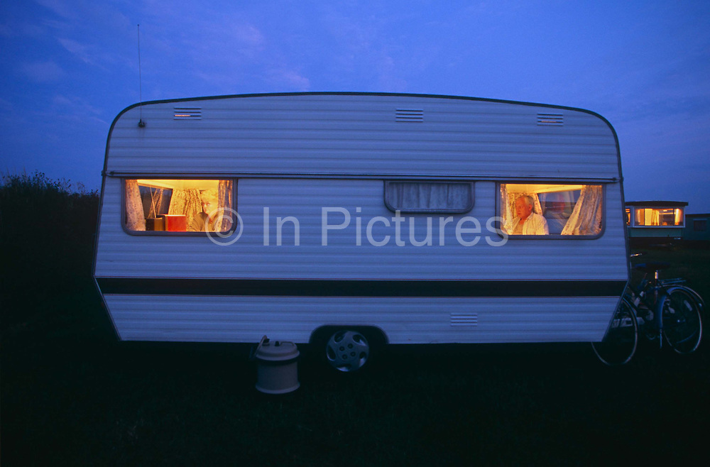 As the late light turns into twilight blue, the warm orange glow of two caravan campers can be seen through both the front and rear windows of their caravan at the Trewethett Farm Caravan Club Site, Tintagel, Cornwall.  The wife watches TV at the back while the husband reads his newspaper shows the small world that caravanners enclose themselves in when on a camping holiday. Caravanning is one the favourite leisure pastimes in Britain, its association, the elite Caravan Club, was founded in 1907 and now represents nearly 1 million members (caravanners, motor caravanners and trailer tenters) and has an  annual turnover of £86 million. On the open road, the caravan is as ridiculed and despised for its slowness and the width it occupies on narrow country lanes.