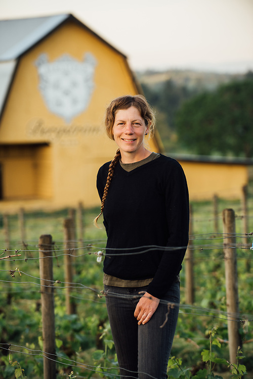 Portrait of Sara Bright vineyard manager for Bergstrom Wines in the Willamette Valley for Oregon Wine Press featuring Women Vineyard Managers standing in front of barn at Bergstrom wines.