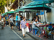 27 NOVEMBER 2015 - BANGKOK, THAILAND: A woman walks past vendors selling amulets on Maharat Road in Bangkok. Hundreds of vendors sell amulet and Buddhist religious paraphernalia to people in the Amulet Market, a popular tourist attraction along Maharat Road north of the Grand Palace near Wat Maharat in Bangkok. Bangkok municipal officials announced that they are closing the market and forcing vendors to relocate to an area about one hour outside of Bangkok. The closing of the amulet market is the latest in a series of municipal efforts to close and evict street vendors and markets from areas that have potential for redevelopment. The street vendors will be evicted from the area by Sunday, Nov. 29.    PHOTO BY JACK KURTZ