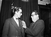Dr Noel Browne TD Receives a Fainne at Belvedere Hotel<br /> 14/11/1953 (Irish Speaking)<br /> <br /> Noël Christopher Browne (20/12/1915 – 21/05/1997) was an Irish politician and doctor. He holds the distinction of being one of only five Teachtaí Dála (TDs) to be appointed Minister on their first day in the Dáil. His controversial Mother and Child Scheme in effect brought down the First Inter-Party Government of John A. Costello in 1951.<br /> Browne was a well-known but at times highly controversial public representative and managed to be a TD for five different political parties (two of which he co-founded). These were Clann na Poblachta (resigned), Fianna Fáil (expelled), National Progressive Democrats (co-founder), Labour Party (resigned) and the Socialist Labour Party (co-founder).