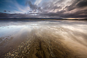 Clouds reflect over the wet sands of the Braint Estuary near Newborough on the island of Anglesey, with the hills of Snowdonia in the background. Multitudes of tiny shells, many empty, some full of life followed the flow of water towards the main channel which echoed the clouds overhead