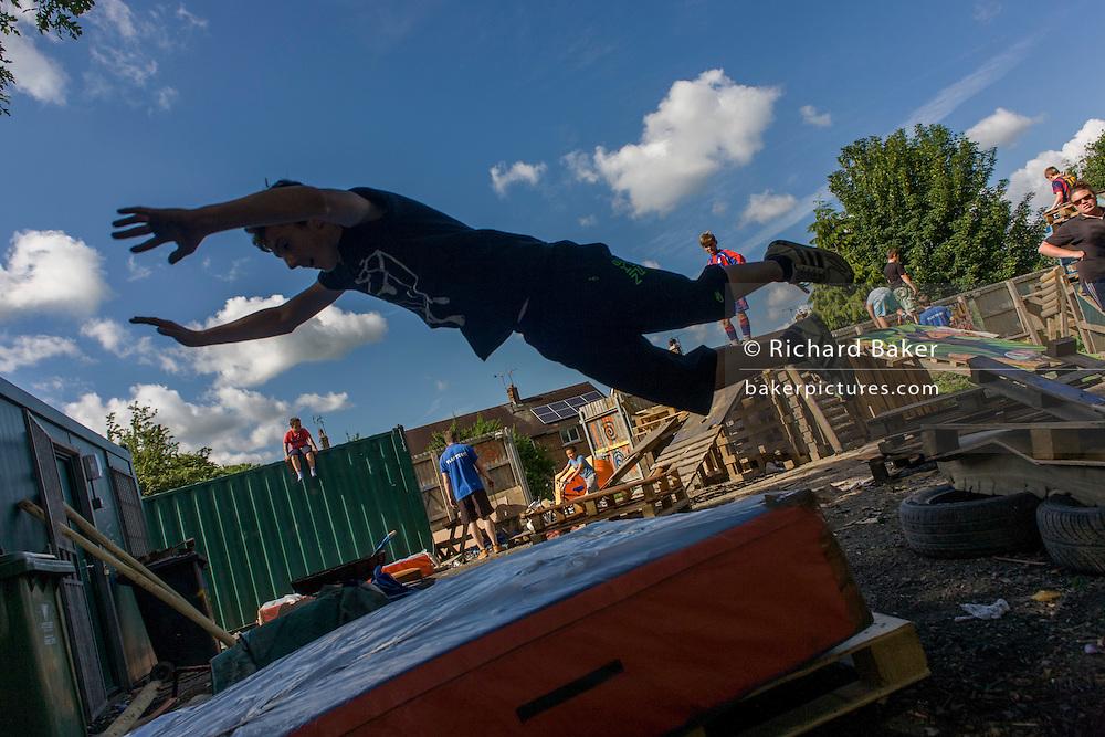 Boy somersaults onto matt in risk averse playground called The Land on Plas Madoc Estate, Ruabon, Wrexham, Wales.