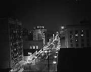 """Y-481122-03. Night view of SW Broadway looking north from Jefferson, from the Oregonian rooftop. Paramount & Broadway theatres. November 22, 1948. """"City lights & Broadway from Oregonian building"""""""