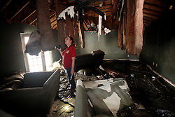 07 September 2012. Braithwaite, Plaquemines Parish, Louisiana,  USA. .Stephanie Gelvin surveys the total destruction of her family home and all their possessions on her first return visit since evacuation before Hurricane Isaac carried a 16ft storm surge through her neighbourhood. The family moved as many items as they could to the second floor thinking they would be secure should the house flood. The water rose well into the second floor leaving very few precious items to salvage..Photo; Charlie Varley.
