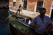A gondola ride in a narrow canal in Venice, Italy. Current prices (2015) is 80 Euros for a 40-minute journey (earning them approx 130,000 Euros a year) along the waterways of this old city but rarely do gondoliers wear their straw hat.