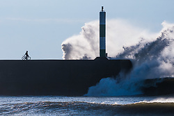 © Licensed to London News Pictures. 14/12/2018. Aberystwyth, UK. Huge surf waves batter the harbour wall and lighthouse as they  roll in off the Atlantic on a sunny but bitterly cold, cold and windy day in Aberystwyth Wales. <br /> Photo credit: Keith Morris/LNP