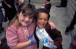Schoolgirls eating crisps in playground; primary school; Yorkshire UK