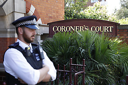 © Licensed to London News Pictures. 26/06/2017. London, UK. A policeman stands outside Westminster coroner's court as an inquest is held into the deaths of some of the victims of the fire at Grenfell Tower in West London. Police say 79 people are missing, feared dead after the tower block was engulfed in flames on June 14th. Photo credit: Peter Macdiarmid/LNP